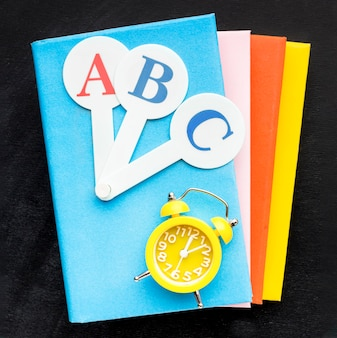 Flat lay of school essentials with books and clock