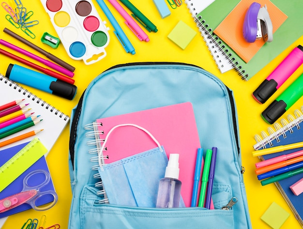 Flat lay of school essentials with multicolored pencils and backpack