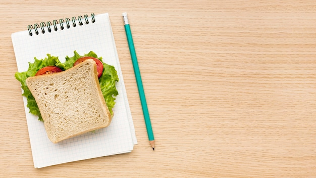 Flat lay of school essentials with notebook and sandwich