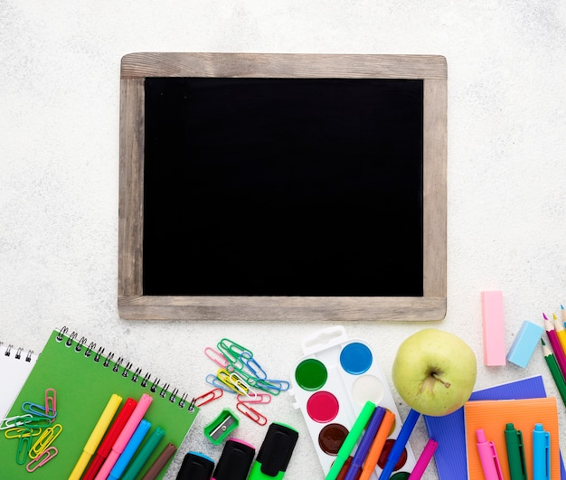 Flat lay of school essentials with pencils and blackboard