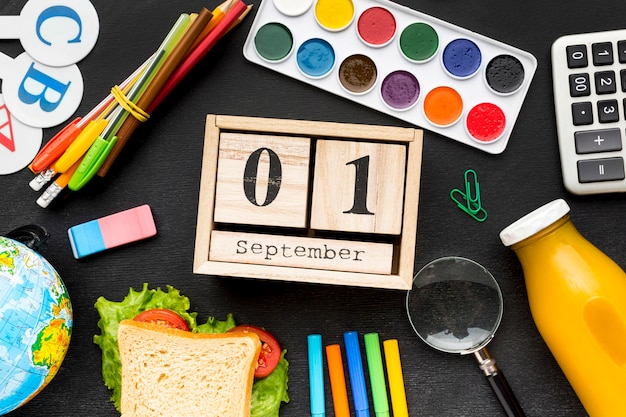Flat lay of school essentials with sandwich and calendar