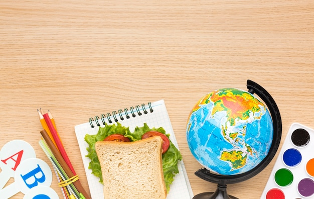 Flat lay of school essentials with sandwich and globe