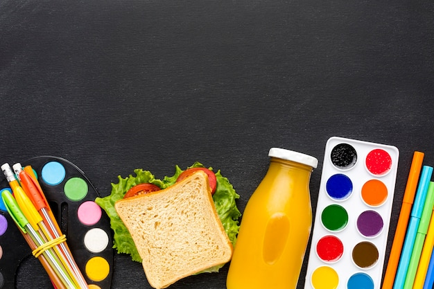 Flat lay of school essentials with sandwich and juice