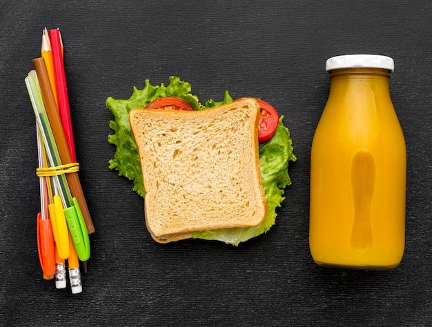 Flat lay of school essentials with sandwich and pencils