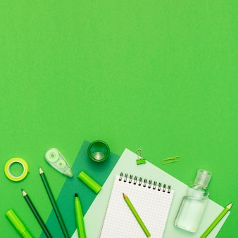 Flat lay school items on green background
