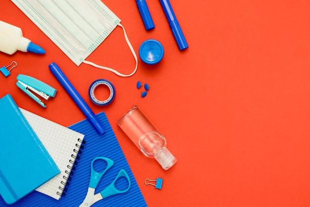 Плоские лежал школьные предметы на красном фоне