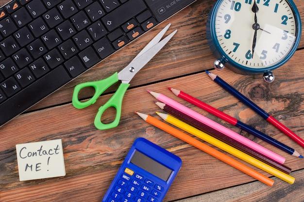 Плоские лежал аксессуары школьника на коричневый деревянный стол. плоский вид сверху. ножницы с карандашами и калькулятором. свяжитесь со мной примечание.