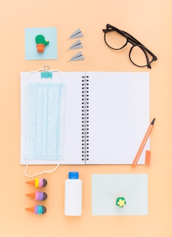 Flat lay of school supplies with notebook and face mask