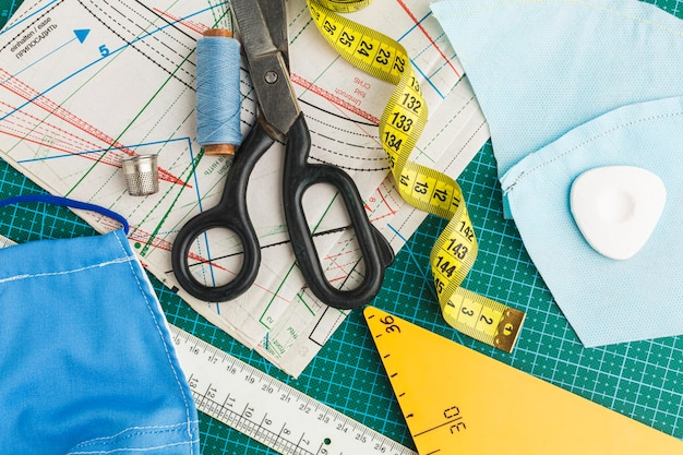 Flat lay of scissors with measuring tape and thread