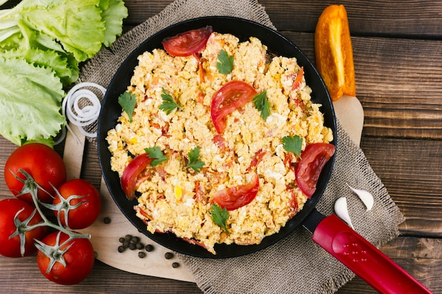 Flat lay scrambled eggs with tomatoes