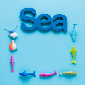 Flat lay of sea with fish figurines