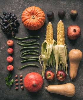 Flat lay seasonal vegetables and fruits on gray background.