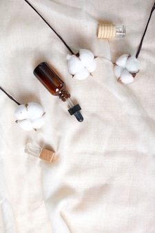 Flat lay of serum glass bottle with pipette and beautiful cotton flower on cloth texture background, concept of natural cosmetic, skinimalism, copy space.