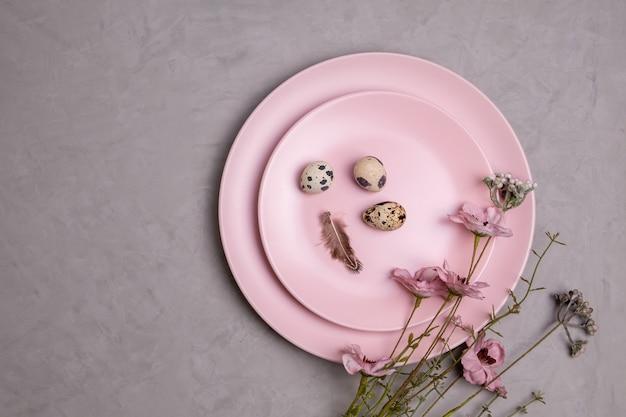 아름다운 작은 메추라기 알, 깃털, 야생화 가지와 함께 두 개의 분홍색 접시를 평평하게 제공