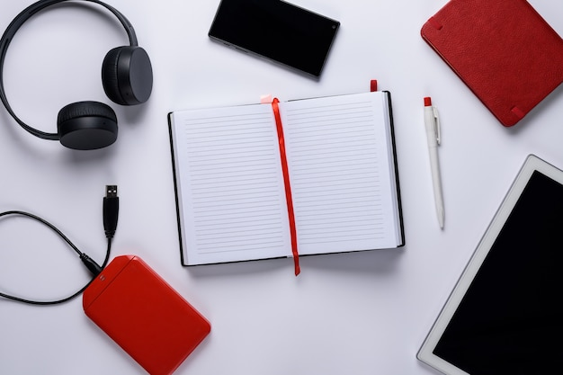 Flat lay set of gadgets in the center open notepad
