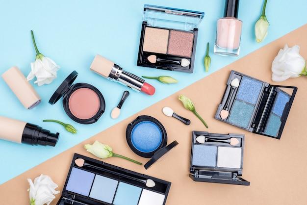 Плоский набор косметических товаров на двухцветном фоне