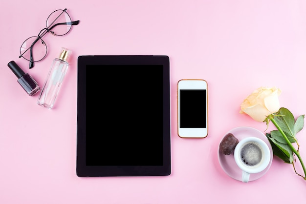 Flat lay set of tablet and phone with cup of coffee, glasses, rose and perfume on pink, mock up