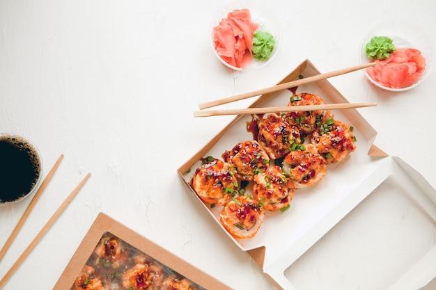 Плоский набор с имбирем и васаби - запеченный суши с лососем в бумажной упаковке на белом фоне - яркий вкусный набор суши-роллов