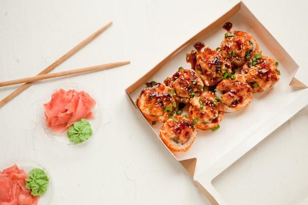 생강과 와사비가 있는 평평한 평지 - 배경에 종이 포장에 연어를 넣은 구운 스시 - 밝고 맛있는 스시 롤 세트