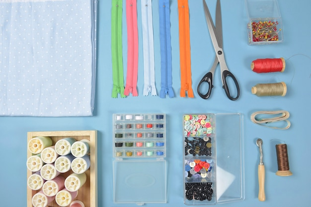 Flat lay of sewing material contains the fabrics, scissors, zipper, pin and thread rolls.