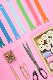 Flat lay of sewing material contains the fabrics, scissors, zipper and thread rolls.