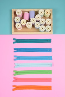 Flat lay of sewing material contains the zipper and colorful thread rolls for sewing.