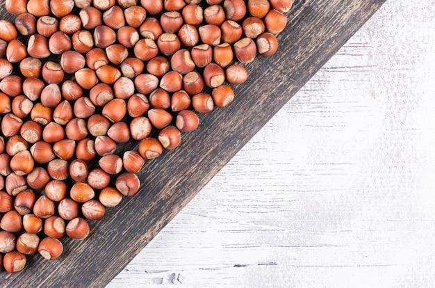 Nocciole sgusciate piano di disposizione sulla tavola di legno scura e bianca.