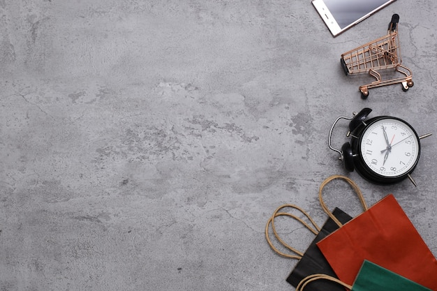Flat lay of shopping bags trolley and mobile phone on grey background ideas about online shopping