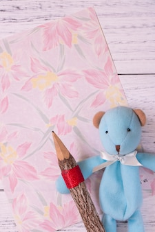 Flat lay shot of flower stationery paper and cute bear holding pencil