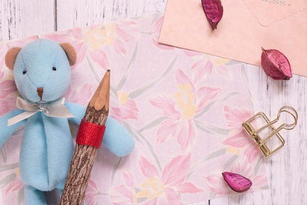 Flat lay shot of flower stationery paper envelope and petals cute bear holding pencil