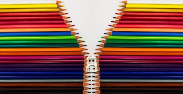 白い表面にカラフルな鉛筆のフラットレイショット