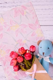 花の文房具の紙と花の束を保持しているかわいいクマのフラットレイショット