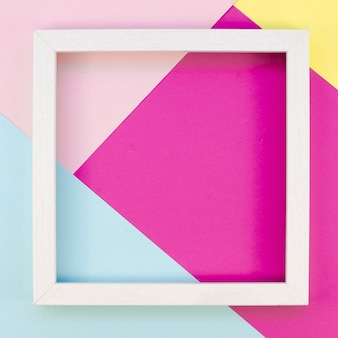 Flat lay of simple frame with colorful paper geometry