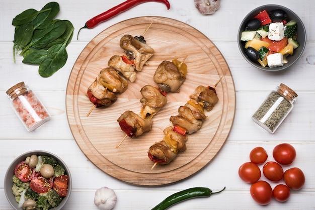 Плоские лежал шампуры на деревянной доске с ингредиентами