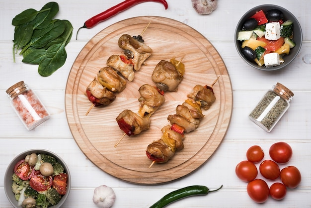 Flat lay skewers on wooden board with ingredients