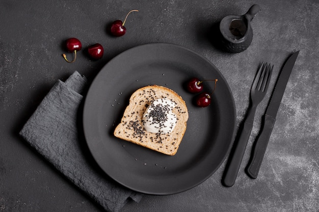 Flat lay slice of bread with cream and arrangement of cherries