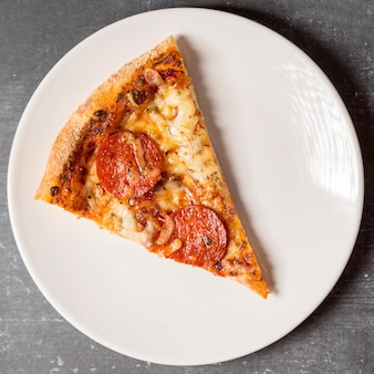 Flat lay slice of pepperoni pizza on plate