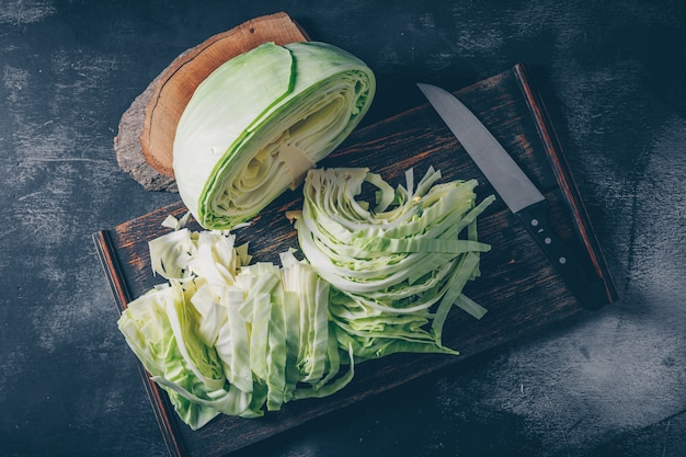 Flat lay sliced and chopped cabbage in cutting board and knife with wood stub on dark textured background. horizontal