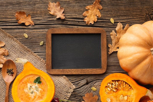 Flat lay sliced pumpkin wooden spoon and leaves with blank blackboard