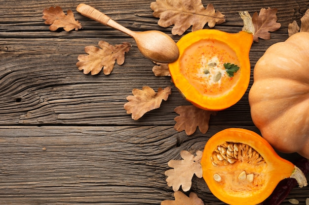 Flat lay sliced pumpkin and wooden spoon with copy space