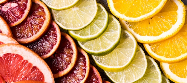 Flat lay slices of different raw fresh citrus fruit.