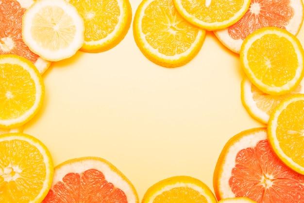 Плоские выложенные ломтики апельсина, грейпфрута и лимона образовали рамку