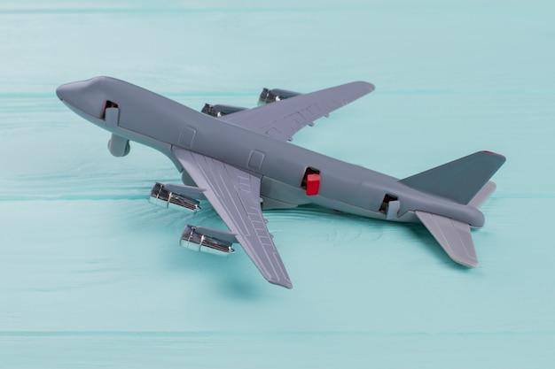 청록색 배경에 평평한 작은 회색 장난감 비행기가 놓여 있습니다. 비행기의 일부 문이 열립니다.