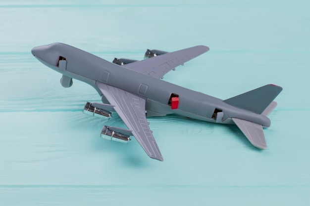 Flat lay small grey toy airplane on turquoise background. some doors on the plane are opened.
