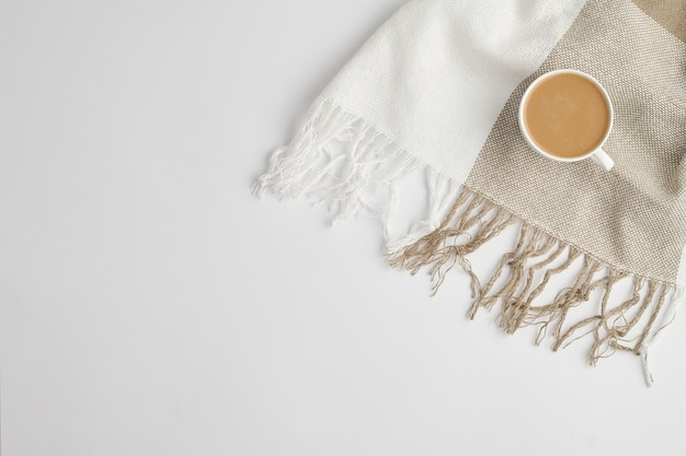Flat lay of small white porcelain cup of fresh aromatic cappuccino on checkered linen or cotton scarf with copyspace on the left