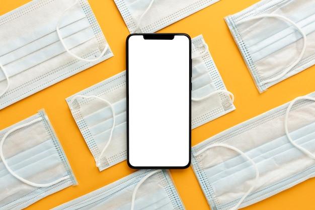 Lay piatto di smartphone sul modello di maschere mediche