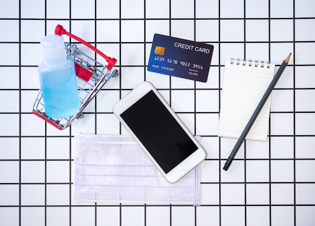 Flat lay of smartphone, surgical mask, credit card, notebook and alcohol gel sanitizer