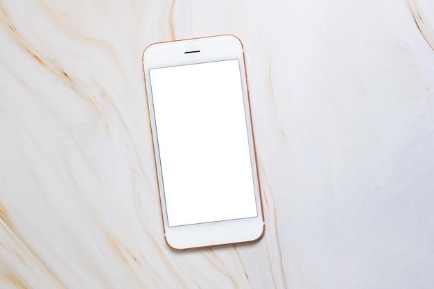 大理石のテーブルに空白の白い画面とコピースペースを備えたフラットレイスマートフォン。
