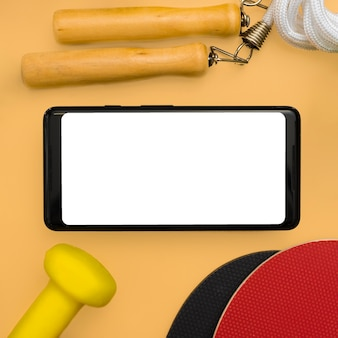 Flat lay of smartphone with jump rope and weight