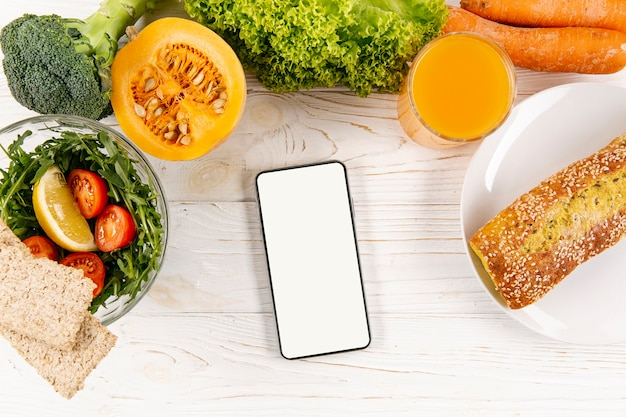 Flat lay of smartphone with meal and bread